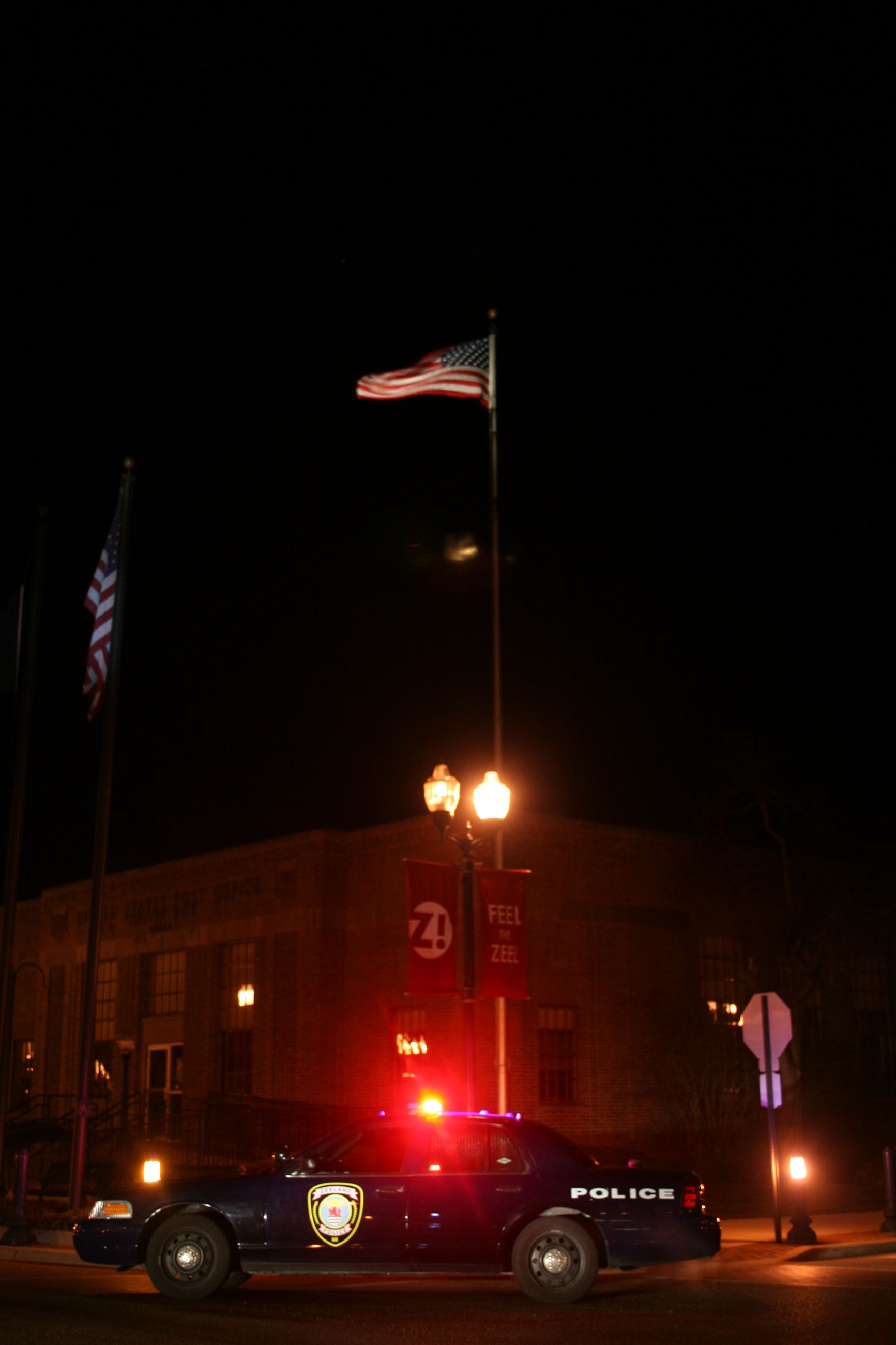 Police Car at Night with Flag