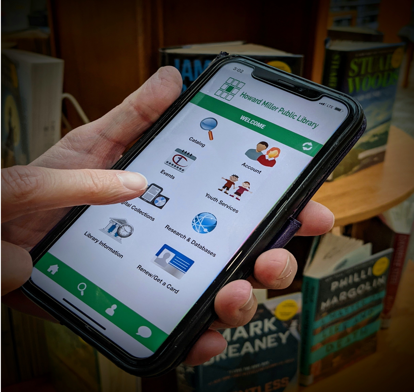 mylibrary app on a phone in front of books at the library